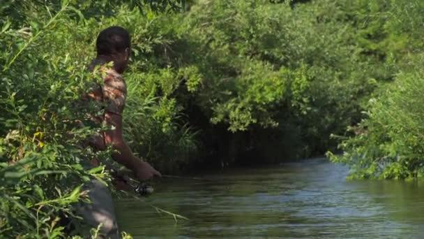 Muž rybolov na horské řece s ultralight spřádání pomocí rybářských woblery