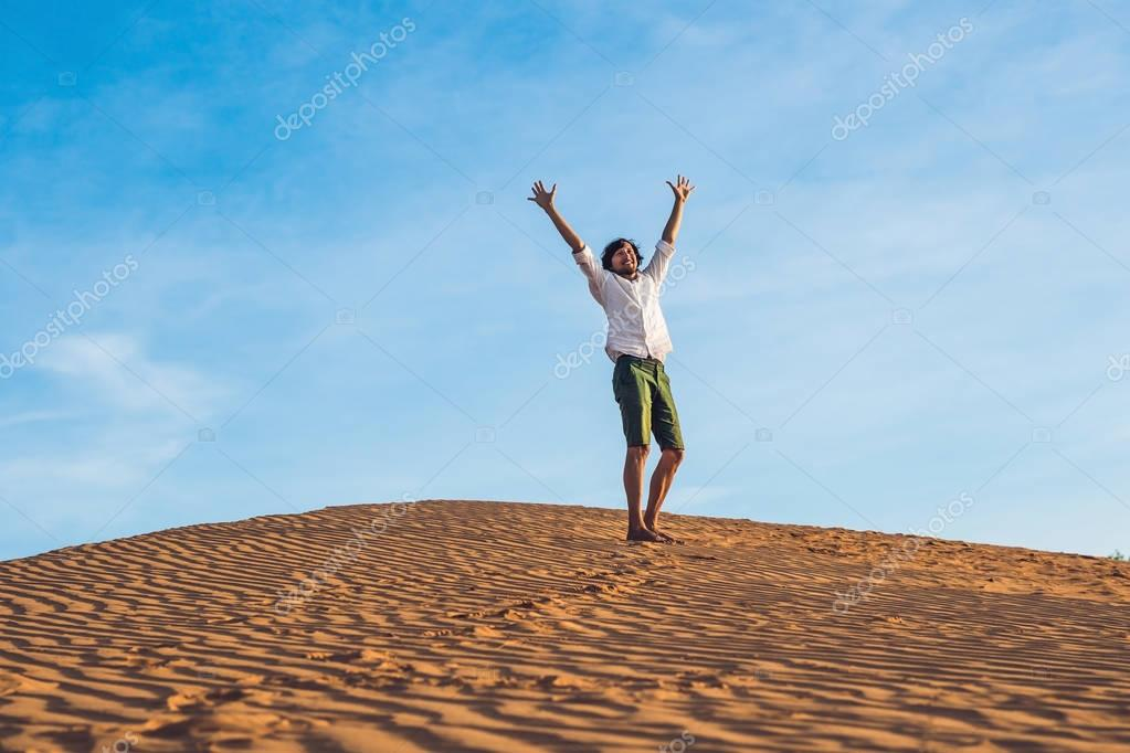Beautiful young man jumping barefoot on sand in desert