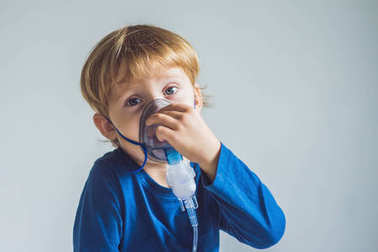 Boy making inhalation with a nebulizer