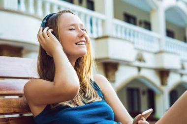 Happy woman relaxing near swimming pool listening with earbuds to streaming music. Beautiful girl using her mobile phone app 4g data to play songs while relaxing on summer luxury vacations.