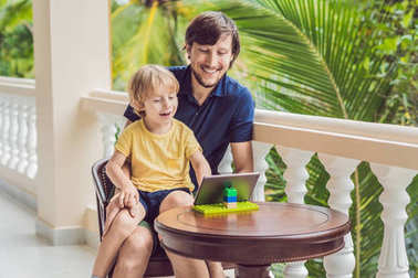 father and son in the tropics talking with friends and family on video call using a tablet and wireless headphones sitting on the terrace.