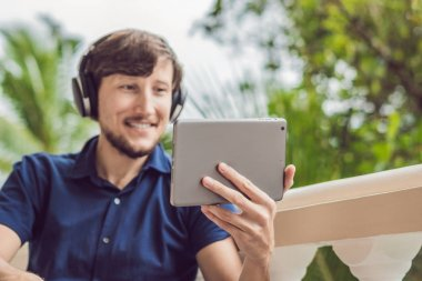 man in the tropics talking with friends and family on video call using a tablet and wireless headphones sitting on the terrace.