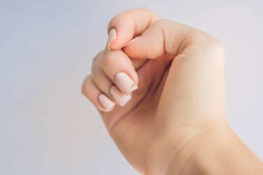 Broken nail on a woman's hand with a manicure on a green background.