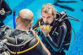 Instruktor potápění a studenti. Instruktor vyučuje studenty potápění.