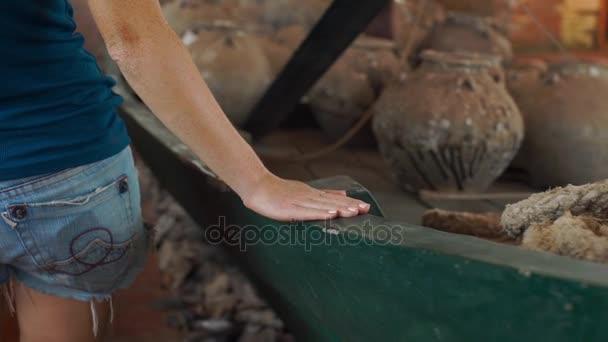 Zeitlupenaufnahme einer Frau besucht Ausstellung im Nationalmuseum auf der Phu-quoc-Insel Vietnam, sie berührt ein altes Boot, das mit Keramikkrügen gefüllt ist