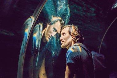 Man looks at the fish in the aquarium