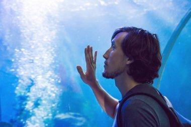 Man looks at the fish in the aquarium.