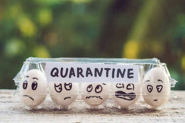 Eggs with funny faces in paper box with word quarantine