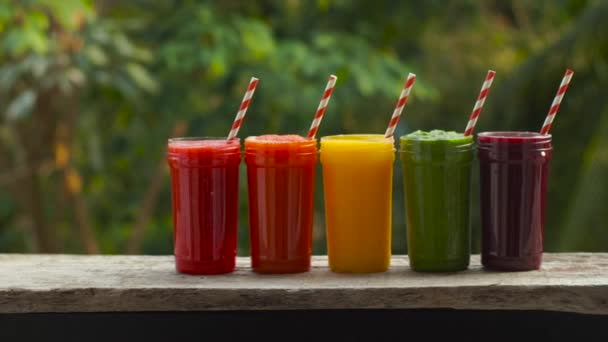 Rainbow from smoothies. Smoothies, juices, beverages, drinks variety with fresh fruits on a wooden table.