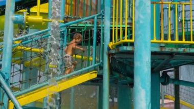 Superslowmotion shot of a little boy climbing up the stairs to the begining of a high water slide in a water entertainment park