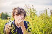 Fotografie Young man sneezes because of an allergy to ragweed.