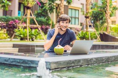 Young freelancer working on vacation next to the swimming pool.