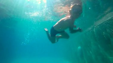 ultrahd slowmotion underwater shot of a little boy learns how to swim in a pool. Toddler boy dives into pool.
