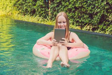 Young female freelancer sitting near pool with her laptop. Busy at holidays. Distant work concept