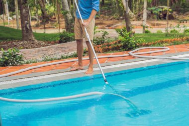 Cleaner of the swimming pool . Man in a blue shirt with cleaning equipment for swimming pools, sunny.