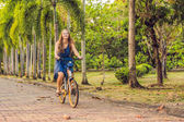woman riding on bicycle in park in summer