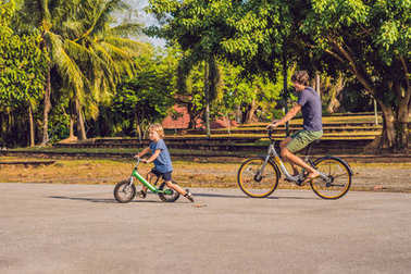 Father and son riding bikes outdoors and smiling