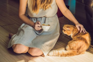 Young woman drinking coffee and stroking cat