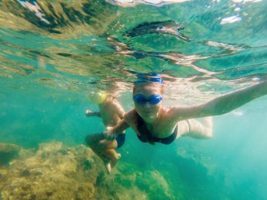 Happy mother and son snorkeling in sea at daytime