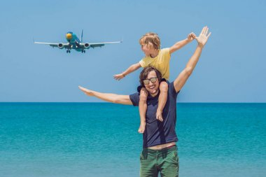 Father and son have fun on the beach watching the landing planes. Traveling on an airplane with children concept