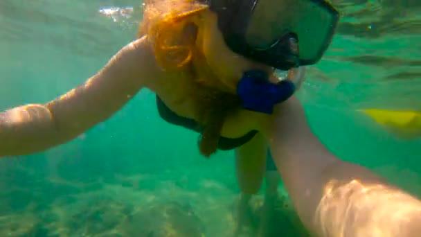 Zeitlupenaufnahme einer jungen Frau beim Schnorcheln im Meer