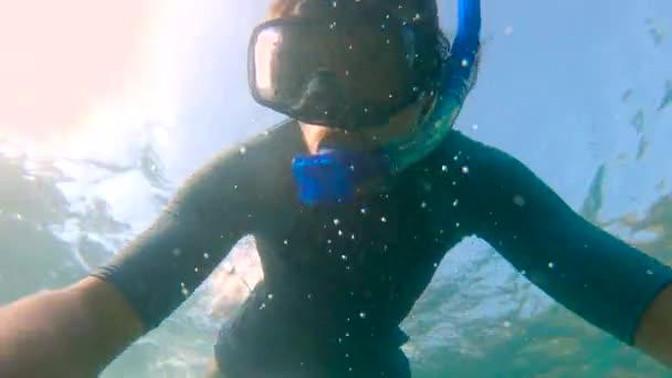 Zeitlupenaufnahme eines jungen Mannes beim Schnorcheln und Tauchen ins Meer. u.p.f 50 auf dem Ärmel eines Hemdes - zeigt den ultravioletten Schutzfaktor eines Hemdes an.