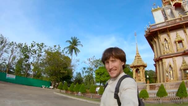 Slowmotion lövés, egy ember, csinál selfie-sza a buddhista Wat Chalong-templom, a Phuket sziget, Thaiföld