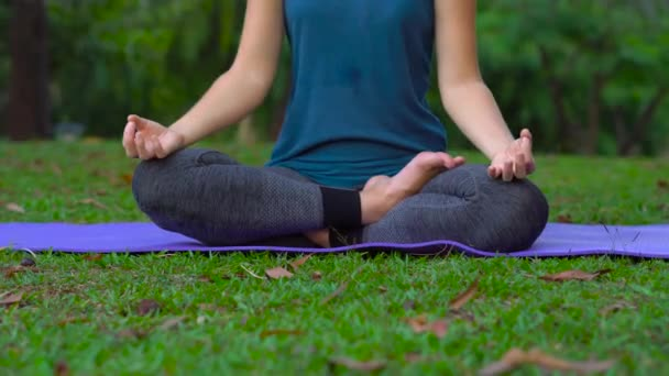 mladá žena, která dělá cvičení jógy v tropickém parku