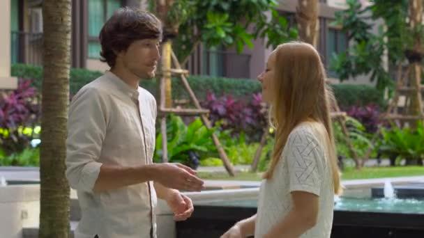 mladá žena realitní agent splňuje klienta ve dvoře činžovního domu a dává klientovi jeho klíč a plastové karty