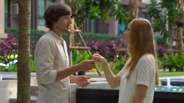 giovane donna agente immobiliare incontra cliente in un cortile di un condominio e fornisce client sua chiave e la carta chiave in plastica