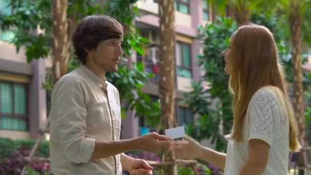 young man real estate agent meets client in a yard of an apartment building and gives client the key and plastic key card