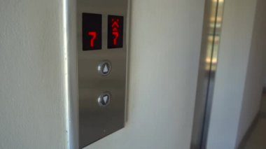 man push the button to call an elevator and enter inside