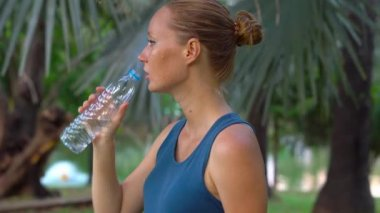 Attractive sporty woman drinking water from bottle after jogging or running