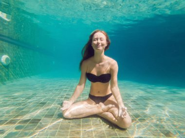 Young woman in black bikini in yoga position underwater in diving aquarium, full body shot, front view.