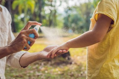 dad and son use mosquito spray.Spraying insect repellent on skin outdoor.
