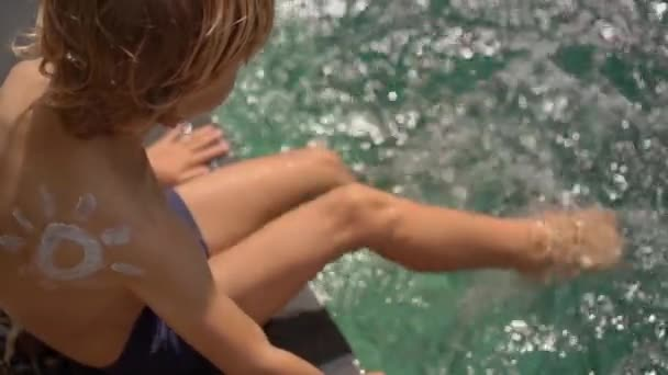 Slowmotion shot of a little boy with a sun drawn by a sunscreen cream on his shoulder splash water in a swimming pool. Sun protection concept