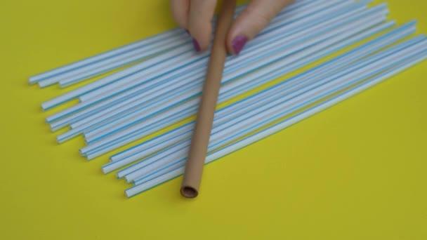 Kézi közelkép sok-sok műanyag szívószálról, színessárga háttérrel - egy ember keze egy bambuszszívószálat tett a műanyagra. Környezetbarát alternatív koncepció