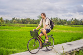 A young man rides a bicycle on a rice field in Ubud, Bali. Bali Travel Concept