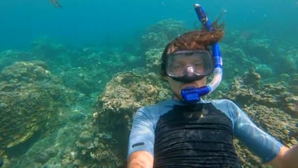 Zeitlupenaufnahme eines jungen Mannes beim Schnorcheln inmitten von Korallen im klaren, blauen Wasser, umgeben von vielen tropischen Fischen