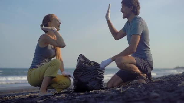 Young couple clean up the beach from a trash