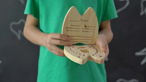 Little boy shows a wooden box for his milk teeth. Concept of children tooth change