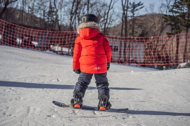 Little cute boy snowboarding. Activities for children in winter. Childrens winter sport. Lifestyle