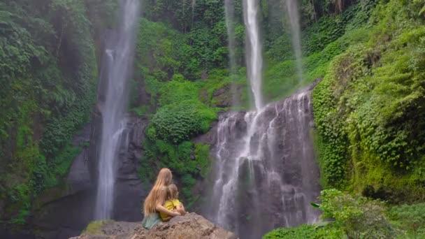 Mladá žena a její malý syn turisté navštívit největší vodopád na ostrově Bali - Sekumpul vodopád. Cestování na Bali koncept.