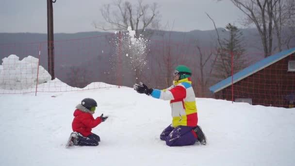 Ein junger Mann und sein kleiner Sohn amüsieren sich auf einer Skipiste im Aktivitätenpark eines Bergortes. Winterferienkonzept. Zeitlupenschuss.