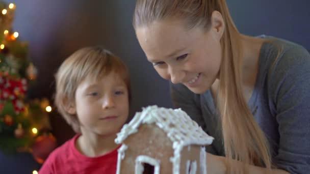 Mladá žena a její syn uvaří perníkovou chaloupku. Rodinná dovolená. Chrystmas concept