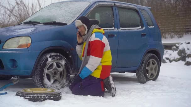 Winter, falling snow. Man on the road have troubles with his car. He is trying to replace the wheel but he cant, then he calls to the road assistance company to get help