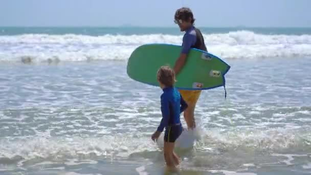 Surf instructor teaches little boy how to surf