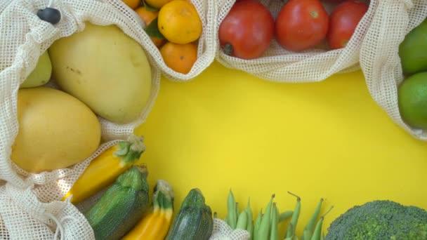 Színes gyümölcsök és zöldségek újrahasznosítható zacskókban, sárga alapon. Zéró hulladék. A műanyaghulladék fogalmának csökkentése
