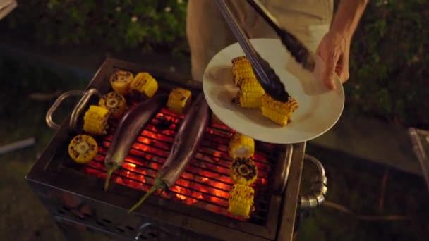 Grilování v noci. Muž vaří zeleninu na grilu