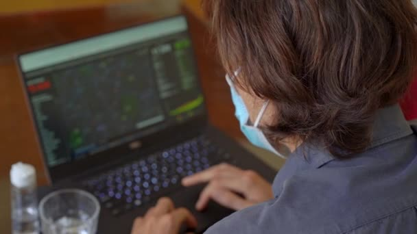 A young man wearing a face mask looking at the screen of his computer where the numbers of people infected with the covid-19 virus are shown. He is terrified by the data. Slowmotion shot